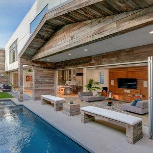 Modelo de piscina con fuente contemporánea, de tamaño medio, rectangular, en patio trasero, con losas de hormigón