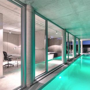Foto de piscina alargada, urbana, grande, rectangular, en patio lateral, con suelo de baldosas