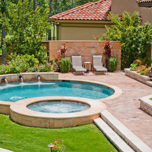 This is an example of a mid-sized traditional backyard round pool in Houston with a hot tub and natural stone pavers.