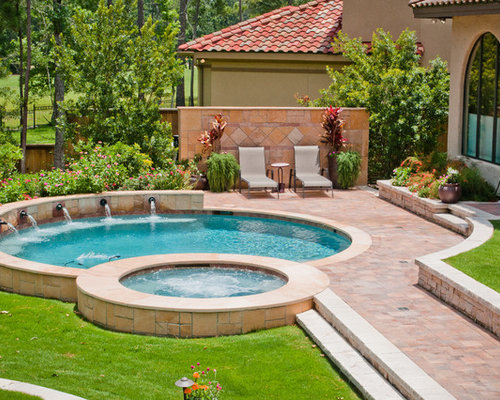 mid sized elegant backyard round pool photo in other with a hot tub