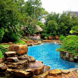 Large traditional backyard round pool in Houston with brick pavers.