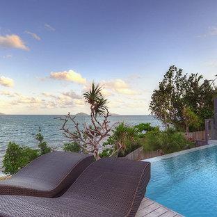 Ispirazione per una piscina a sfioro infinito tropicale rotonda dietro casa con pedane