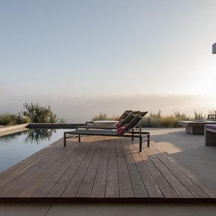 Ispirazione per una piscina minimal rettangolare di medie dimensioni e dietro casa con pedane