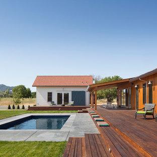 Ejemplo de casa de la piscina y piscina de estilo de casa de campo, de tamaño medio, rectangular, en patio trasero, con entablado