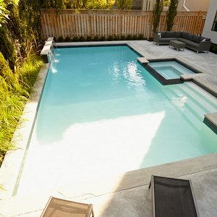 Foto de piscinas y jacuzzis minimalistas, grandes, a medida, en patio trasero, con losas de hormigón