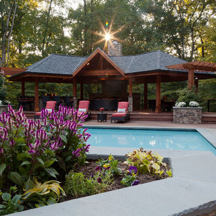 Large tropical backyard rectangular lap pool in DC Metro with decking and a pool house.