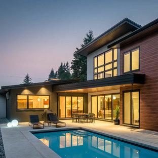 Imagen de piscina retro, de tamaño medio, rectangular, en patio trasero, con losas de hormigón