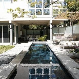 Diseño de piscina alargada, actual, de tamaño medio, rectangular, en patio trasero, con gravilla