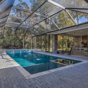 Modelo de piscina con fuente alargada, actual, rectangular, en patio, con adoquines de hormigón