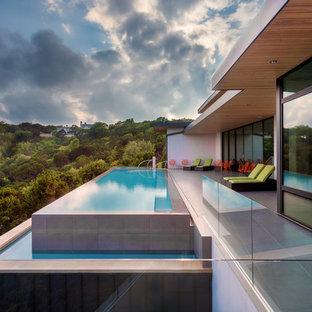 Large minimalist backyard rectangular and concrete paver infinity pool photo in Austin