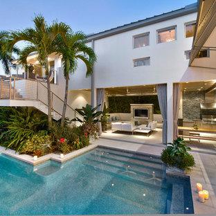 Ispirazione per una piscina stile marinaro personalizzata di medie dimensioni e dietro casa con una vasca idromassaggio e pavimentazioni in cemento