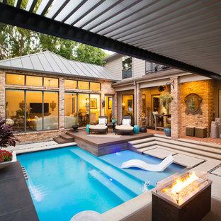 Imagen de piscina minimalista, pequeña, en forma de L, en patio trasero, con adoquines de piedra natural