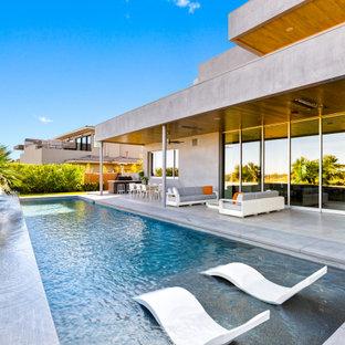 Ispirazione per una grande piscina minimal rettangolare dietro casa con cemento stampato