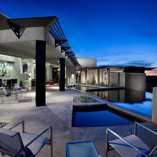 Idee per una grande piscina a sfioro infinito design personalizzata dietro casa con lastre di cemento e una vasca idromassaggio