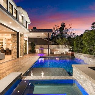 Immagine di una piscina country rettangolare dietro casa con una vasca idromassaggio e pedane