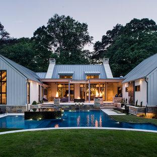 Idéer för en stor lantlig infinitypool på baksidan av huset, med marksten i betong