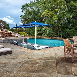 Inspiration pour une très grand piscine arrière et à débordement rustique sur mesure avec un toboggan et des pavés en béton.