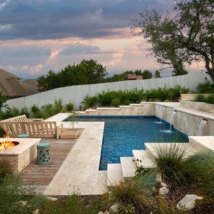Imagen de piscina con fuente natural, actual, de tamaño medio, en forma de L, en patio trasero, con adoquines de piedra natural