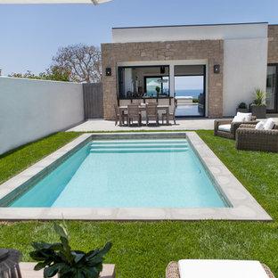 Foto de piscina actual, de tamaño medio, rectangular, en patio, con losas de hormigón