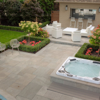 Inspiration for a large contemporary backyard stone and round lap hot tub remodel in Toronto