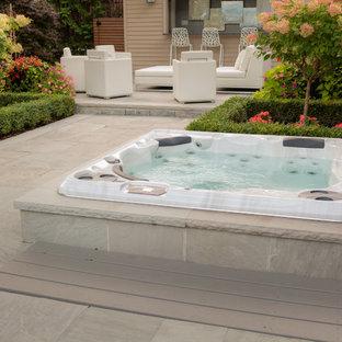 Ejemplo de piscinas y jacuzzis alargados, actuales, grandes, redondeados, en patio trasero, con adoquines de piedra natural