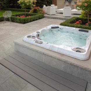 Imagen de piscinas y jacuzzis alargados, actuales, grandes, redondeados, en patio trasero, con adoquines de piedra natural