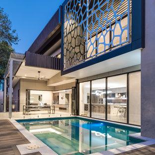 Immagine di una piscina naturale industriale personalizzata di medie dimensioni e in cortile con pedane