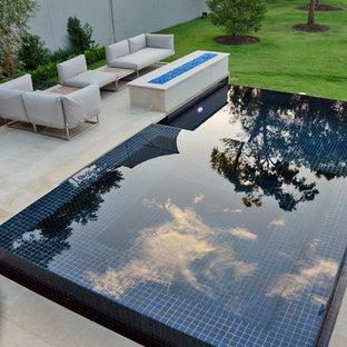 Ejemplo de piscina con fuente infinita, moderna, pequeña, rectangular, en patio trasero, con suelo de baldosas