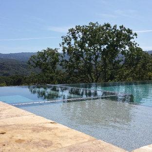 Foto på en stor funkis infinitypool på baksidan av huset, med poolhus och kakelplattor