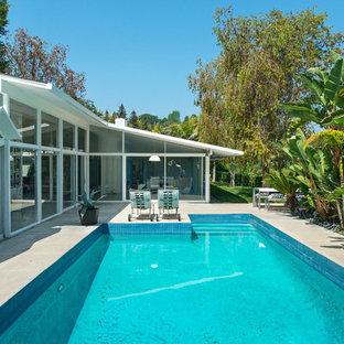 Ejemplo de piscina retro, de tamaño medio, rectangular, en patio trasero, con losas de hormigón