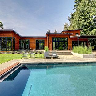 Idéer för att renovera en stor funkis rektangulär pool på baksidan av huset, med marksten i betong