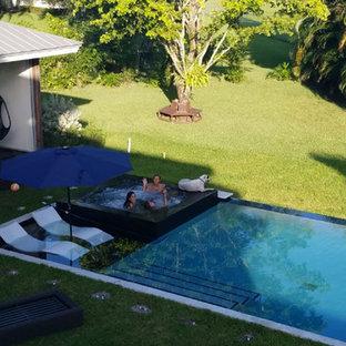Foto di una grande piscina minimalista rettangolare dietro casa con una vasca idromassaggio