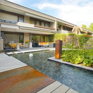 Mittelgroßer Moderner Pool hinter dem Haus in L-Form mit Dielen und Wasserspiel in Sonstige