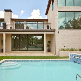 Diseño de piscina con fuente tradicional renovada, de tamaño medio, a medida, en patio trasero, con adoquines de ladrillo