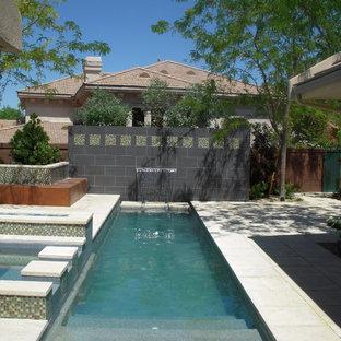 Ispirazione per una piscina naturale minimalista rettangolare di medie dimensioni e dietro casa con un acquascivolo e pedane