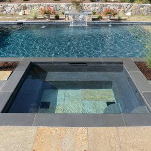 Aménagement d'une piscine arrière classique de taille moyenne et rectangle avec un bain bouillonnant et des pavés en pierre naturelle.