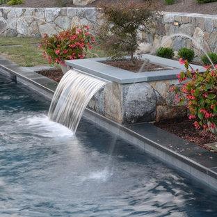 Modelo de piscinas y jacuzzis clásicos, de tamaño medio, rectangulares, en patio trasero, con adoquines de piedra natural