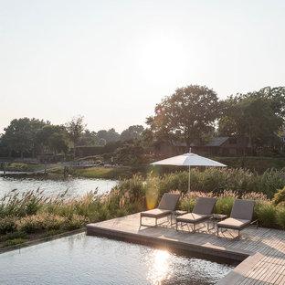 Ispirazione per una piscina naturale country personalizzata di medie dimensioni e dietro casa con pedane