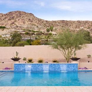 Ejemplo de piscina de estilo americano, grande, rectangular, en patio trasero, con adoquines de piedra natural