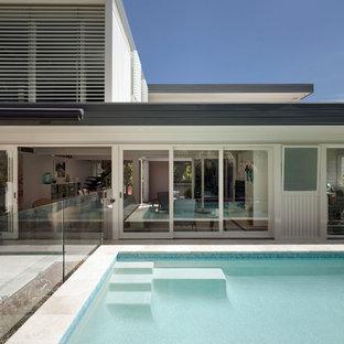 Foto de casa de la piscina y piscina retro, pequeña, rectangular, en patio trasero, con adoquines de piedra natural