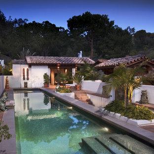 Immagine di una grande piscina monocorsia mediterranea rettangolare dietro casa con fontane e piastrelle
