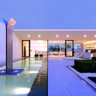 Diseño de piscina con fuente alargada, minimalista, extra grande, rectangular, en patio trasero, con adoquines de hormigón