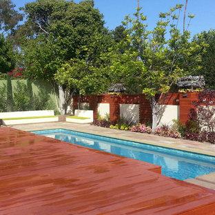 Idee per una piccola piscina monocorsia moderna rettangolare dietro casa con una vasca idromassaggio e pavimentazioni in pietra naturale