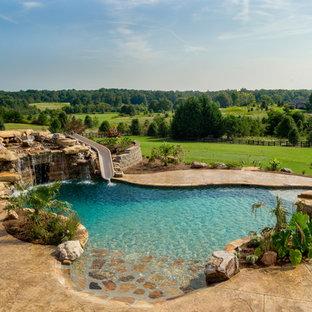 Foto de piscina con tobogán natural, rústica, extra grande, a medida, en patio trasero, con suelo de hormigón estampado