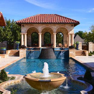 Esempio di una grande piscina vittoriana rettangolare dietro casa con fontane e piastrelle