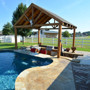Design ideas for a large country backyard custom-shaped lap pool in Little Rock with a hot tub and stamped concrete.