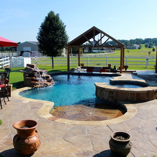 Photo of a large country backyard custom-shaped lap pool in Little Rock with a hot tub and stamped concrete.