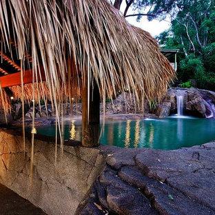 Foto di una piscina naturale tropicale personalizzata di medie dimensioni e davanti casa con un acquascivolo e cemento stampato