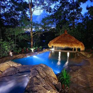 Esempio di una piscina naturale tropicale personalizzata di medie dimensioni e davanti casa con un acquascivolo e cemento stampato