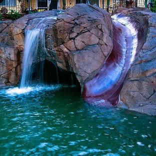 Idee per una piscina naturale tropicale personalizzata di medie dimensioni e davanti casa con un acquascivolo e cemento stampato
